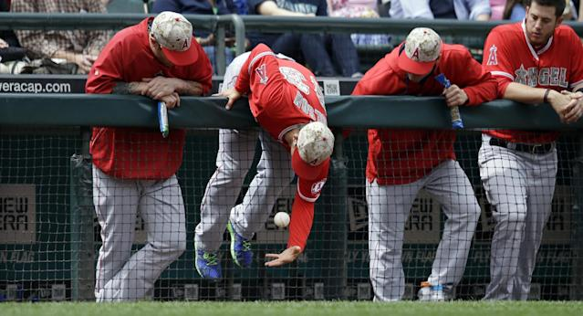 Los Angeles Angels' C.J. Wilson leans over a dugout railing to reach a foul ball against the Seattle Mariners in a baseball game Monday, May 26, 2014, in Seattle. (AP Photo/Elaine Thompson)