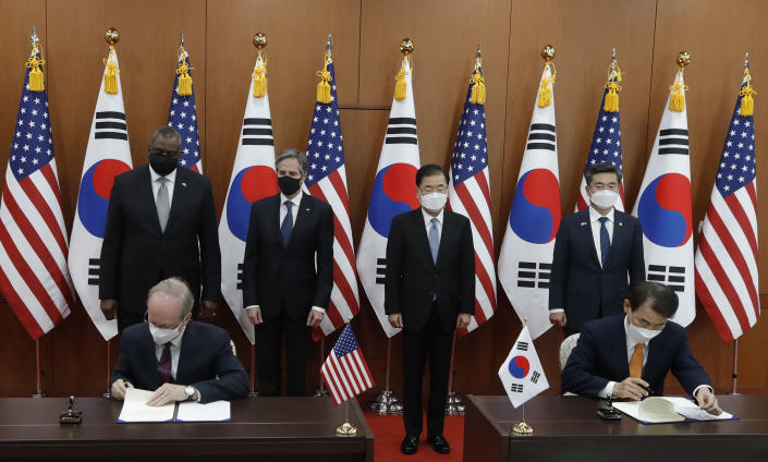 Robert Rapson, Chargé d'Affaires ad interim at U.S. Embassy, left sit, and South Korea's chief negotiator Jeong Eun-bo, right sit, initial as U.S. Secretary of State Antony Blinken, second from left, U.S. Defense Secretary Lloyd Austin, left, South Korean Foreign Minister Chung Eui-yong, second from right, and South Korean Defense Minister Suh Wook, right, clap during an initialing ceremony for Special Measures Agreement at the Foreign Ministry in Seoul, South Korea, Thursday, March 18, 2021. (AP Photo/Lee Jin-man, Pool)
