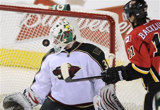 Minnesota Wild's' goalie Josh Harding, left, and Calgary Flames' Mikael Backlund, from Sweden, watch the puck bounce through the crease during second period NHL action in Calgary, Alberta, Tuesday Dec. 20, 2011. (AP Photo/The Canadian Press, Larry MacDougal)