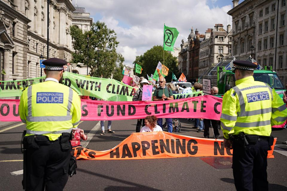 Climate activists from Extinction Rebellion during a protest outside the offices of HM Revenue and Customs (HMRC) (PA)