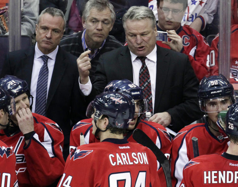 FILE - This March 11, 2012 file photo shows Washington Capitals head coach Dale Hunter, standing right, talks to players as assistant coach Dean Evason, standing left, looks on during a time out in the third period of an NHL hockey game, in Washington. Hunter is finished as coach of the Capitals after less than one full season, telling the team he wants to return to his family in Canada. He told general manager George McPhee of the decision Monday, May 14, 2012, two days after the Capitals were eliminated from the playoffs by the Rangers in Game 7. (AP Photo/Carolyn Kaster, File)
