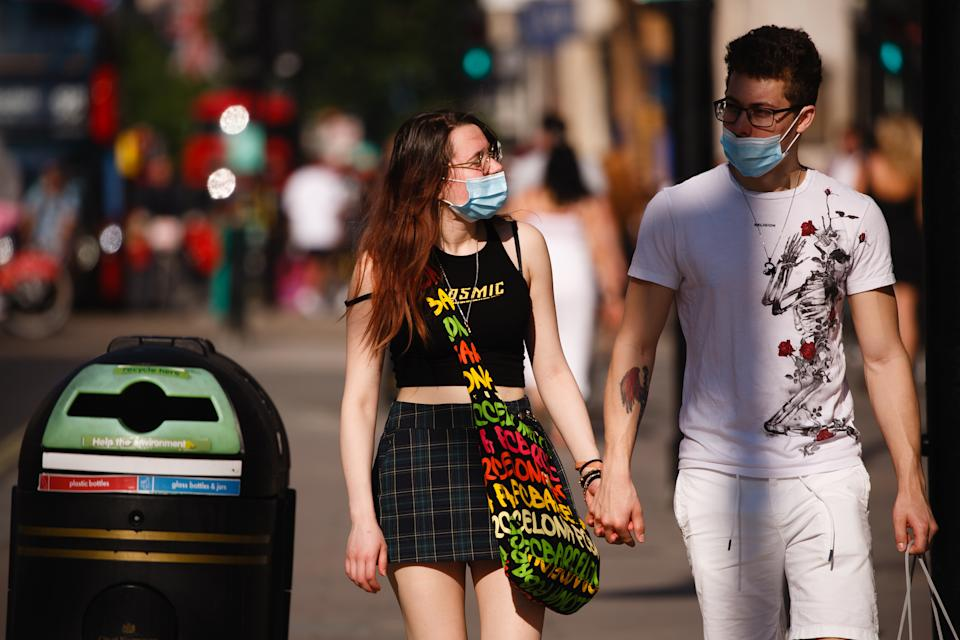 A couple wearing face masks walk amid shoppers on Oxford Street in heatwave conditions in London, England, on June 25, 2020. (Photo by David Cliff/NurPhoto via Getty Images)