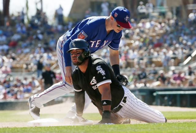 Chicago White Sox's Yoan Moncada, front, is tagged out at third base by Texas Rangers third baseman Drew Robinson during the third inning of a spring training baseball game Tuesday, March 20, 2018, in Glendale, Ariz. (AP Photo/Ross D. Franklin)