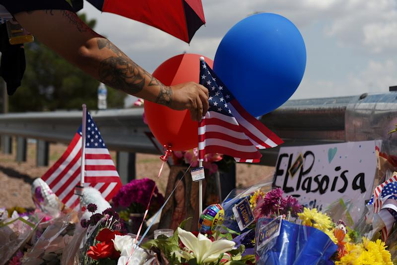 A man places an American flag in the pile of flowers that has gathered a day after a mass shooting at a Walmart store in El Paso, Texas, U.S. August 4, 2019. REUTERS/Callaghan O'Hare TPX IMAGES OF THE DAY
