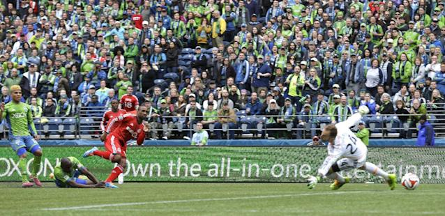 Toronto FC's Jermain Defoe, third from left, kicks a goal past Seattle Sounders goalkeeper Stephan Frei, right, in the first half of an MLS soccer match on Saturday, March 15, 2014, in Seattle. (AP Photo/Ted S. Warren)