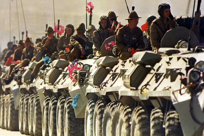 FILE - In this 1988 file photo, Soviet soldiers ride on top of their armored vehicles as they travel along a highway in Kabul heading for the Soviet Union. Afghanistan is marking the 31st anniversary of the Soviet Union's last soldier leaving the country, Saturday, Feb. 15, 2020. This year's anniversary comes as the United States negotiates its own exit after 18 years of war, America's longest. (AP Photo/ Liu Heung-Shing)