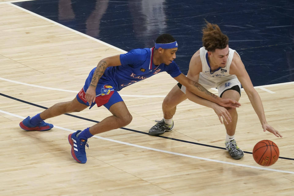 Kentucky's Devin Askewk, right, is defended by Kansas' Dajuan Harris (3) during the first half of an NCAA college basketball game Tuesday, Dec. 1, 2020, in Indianapolis. (AP Photo/Darron Cummings)
