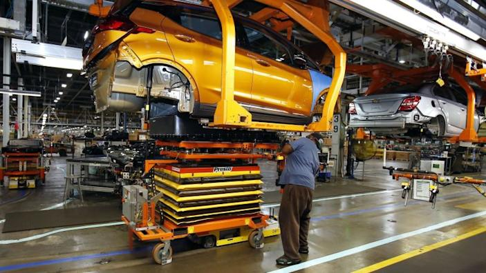 "A Chevrolet Bolt, the company's electric vehicle, is fitted with a battery at a GM assembly plant in Michigan. Automakers are preparing for a sea change in consumer acceptance of EVs. <span class=""copyright"">(Duane Burleson / Associated Press)</span>"