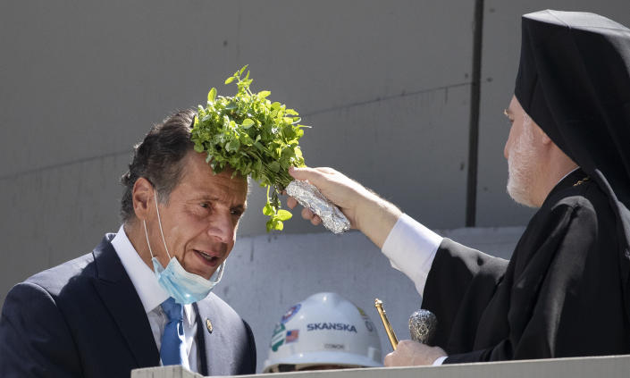 New York Gov. Andrew Cuomo, left, is blessed by Archbishop Elpidophoros holding sprigs of basil during a ceremony at the St. Nicholas Greek Orthodox Church, Monday, Aug. 3, 2020 at the World Trade Center in New York. The original church was destroyed in the attacks of Sept. 11, 2001. The shrine is expected to open in 2021. (AP Photo/Mark Lennihan)