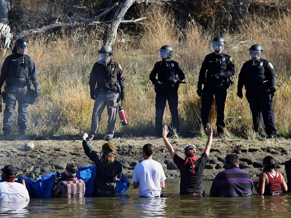 Dozens of protestors demonstrating against the expansion of the Dakota Access Pipeline wade in cold creek waters confronting local police, near Cannon Ball, North Dakota in November 2016 (AP Photo/John L. Mone File)