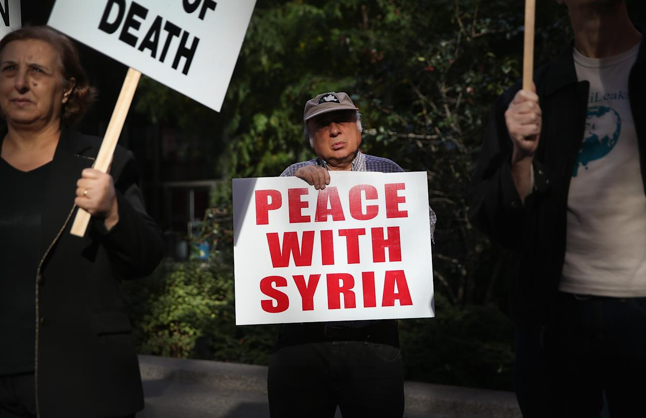 """CHICAGO, IL - OCTOBER 13: Eldon Grossman (C) demonstrates against U.S. intervention in Syria on October 13, 2013 in Chicago, Illinois. The protest was one of many scheduled around the world today under the banner """"Hands Off Syria"""". (Photo by Scott Olson/Getty Images)"""