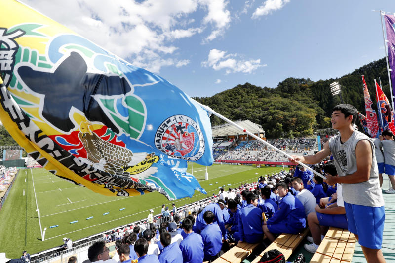 A student waves a huge celebratory flag, known as Tairyo-ki, or a good-catch flag, at the stand at Kamaishi Recovery Memorial Stadium before the Rugby World Cup Pool D game between Fiji and Uruguay in Kamaishi, northeastern Japan, Wednesday, Sept. 25, 2019. In the small fishing town, more than 1,000 were killed by the 2011 earthquake and tsunami. (Naoto Osato/Kyodo News via AP)