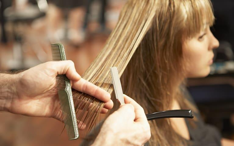Male hairdresser cutting young woman's hair with razor