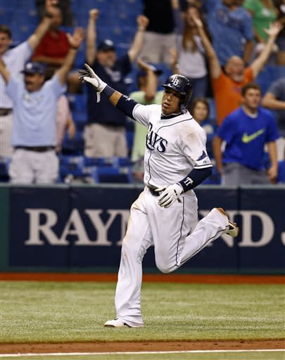 Tampa Bay Rays' Yunel Escobar celebrates as he rounds third base on his way to score the game-winning run on a single by Ben Zobrist in the 13th inning of a baseball game against the Minnesota Twins Wednesday, July 10, 2013, in St. Petersburg, Fla. The Rays won 4-3. (AP Photo/Mike Carlson)