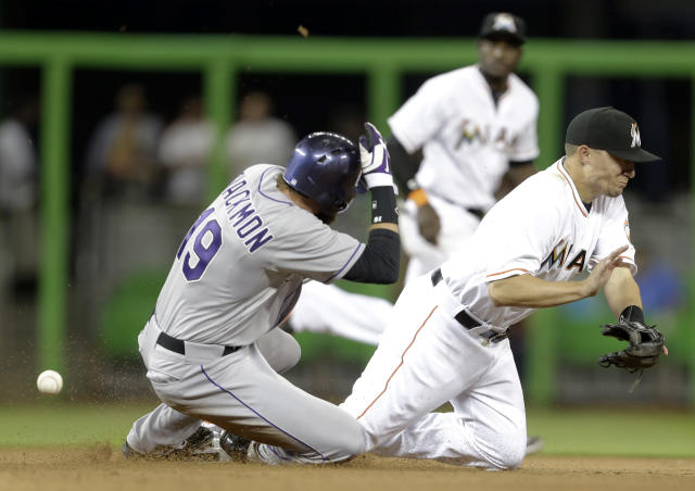 Colorado Rockies' Charlie Blackmon (19) beats the throw to Miami Marlins second baseman Jeff Baker, right, in the seventh inning of a baseball game, Tuesday, April 1, 2014, in Miami. The Marlins defeated the Rockies 4-3. (AP Photo/Lynne Sladky)