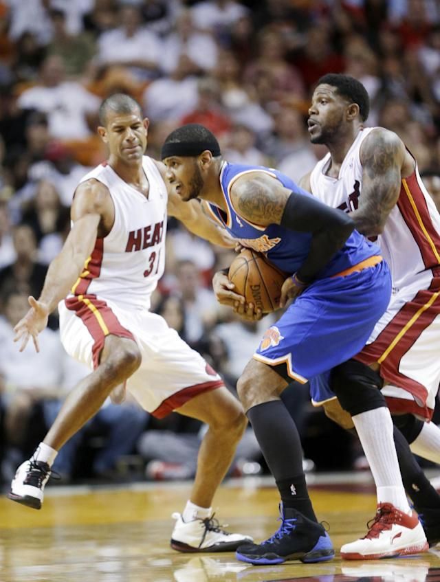 New York Knicks forward Carmelo Anthony, center, is fouled by Miami Heat forward Udonis Haslem, right, as forward Shane Battier, left, defends during the first half of an NBA basketball game, Sunday, April 6, 2014, in Miami. (AP Photo/Wilfredo Lee)