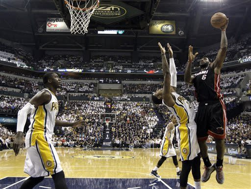 Miami Heat's LeBron James (6) shoots over Indiana Pacers' Paul George (24) during the first half of Game 3 of the NBA Eastern Conference basketball finals in Indianapolis, Sunday, May 26, 2013. At left is Pacers' Roy Hibbert. (AP Photo/Nam H. Huh)