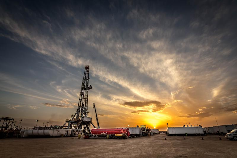 A drilling site with the sun setting in the distance.