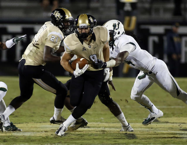 Central Florida wide receiver J.J. Worton (9) runs through the grab of South Florida defensive back Fidel Montgomery (14) during the first half of an NCAA college football game Friday, Nov. 29, 2013, in Orlando, Fla. (AP Photo/Reinhold Matay