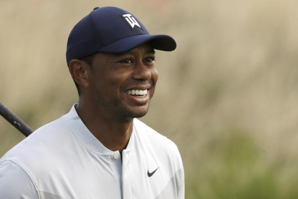 Tiger Woods smiles after teeing off on the 12th hole in the Northern Trust tournament at Liberty National Golf Course, Thursday, Aug. 8, 2019, in Jersey City, N.J. (AP Photo/Mark Lennihan)