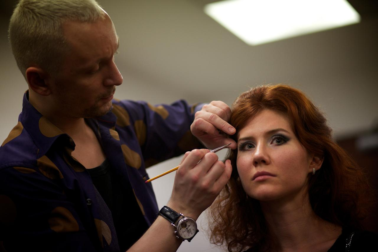 A stylist makes-up Anna Chapman, right, who was deported from the U.S. on charges of espionage, preparing to display a creations by I Love Fashion, France, during Fall-Winter 2012 - 2013 collection at Mercedes-Benz Fashion Week in Moscow,  Russia, Thursday, March 22, 2012. (AP Photo/Alexander Zemlianichenko)