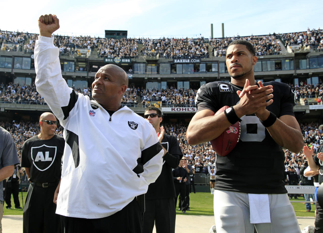 Oakland Raiders coach Hue Jackson, left, and quarterback Jason Campbell are seen during a pre-game ceremony before their NFL football game against the Cleveland Browns in Oakland, Calif., Sunday, Oct. 16, 2011. (AP Photo/Paul Sakuma)