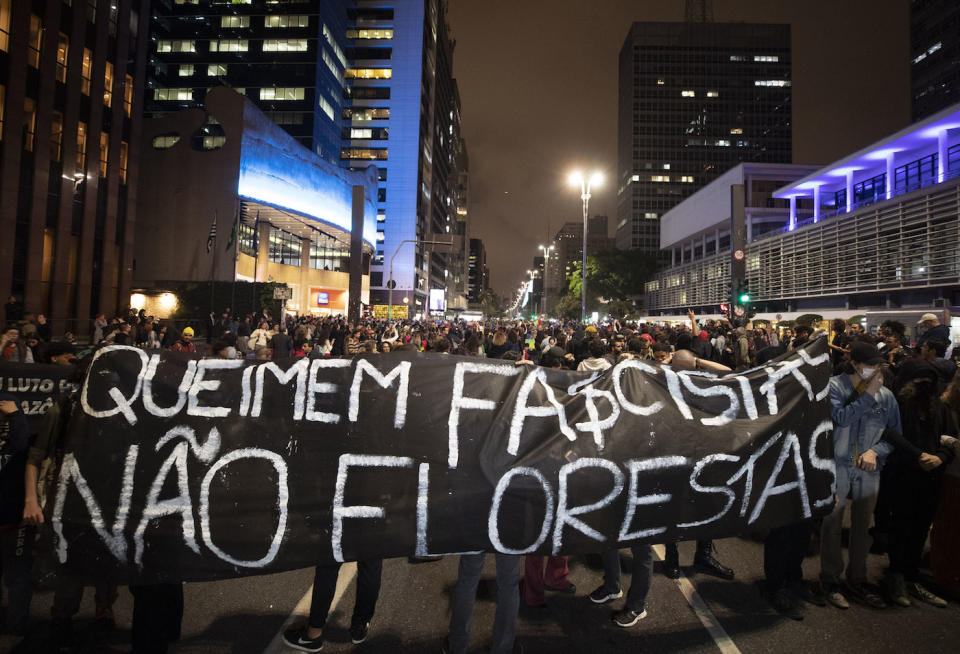 "Demonstrators in Sao Paulo march holding a banner that reads in Portuguese: ""Burn the fascists not the rainforest"" (Picture: AP)"