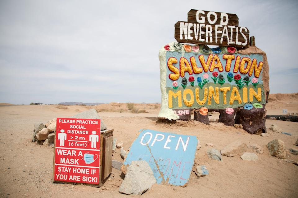 A sign urging social distancing and mask wearing sits near Salvation Mountain, just outside of Slab City, Calif., on Monday, April 5, 2021.