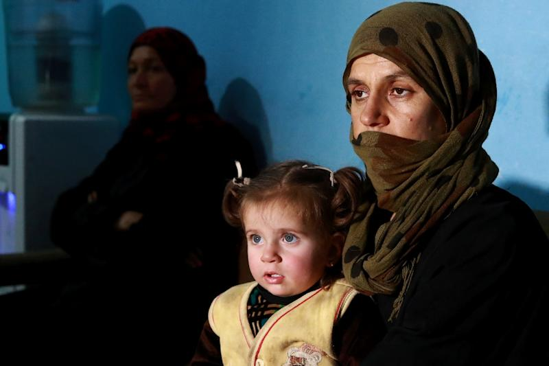 """Sabha, one of a group of Iraqi Yazidi women and girls to escape from Islamic State (IS) group fighters after being held for years as """"sex slaves"""", sits with her daughter at a centre near the Omar oil field in eastern Syria (AFP Photo/DELIL SOULEIMAN)"""