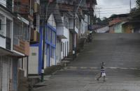 Wearing a mask to curb the spread of the new coronavirus, a resident walks on a street in Campohermoso, Colombia, Thursday, March 18, 2021. According to the Health Ministry, Campohermoso is one of two municipalities in Colombia that has not had a single case of COVID-19 since the pandemic started one year ago. (AP Photo/Fernando Vergara)