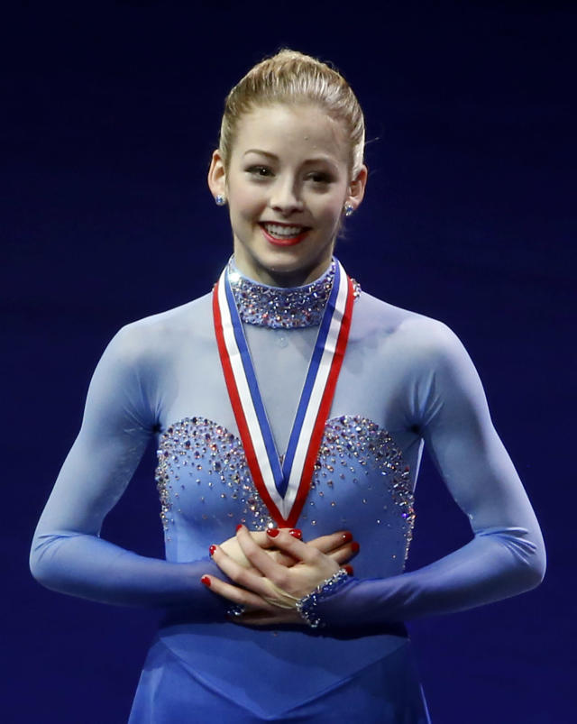 Gracie Gold holds her gold medal on the podium at the women's skating awards ceremony at the U.S. Figure Skating Championships in Boston, Saturday, Jan. 11, 2014. (AP Photo/Elise Amendola)