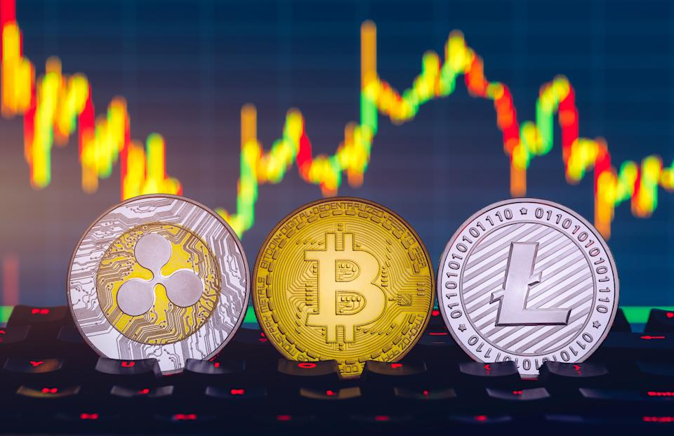Prague, Czechia - November 5, 2018: Bitcoin, litecoin and ripple coins currency finance money on graph chart background. Bitcoin as most important cryptocurrency concept. Stack of cryptocurrencies with a golden bitcoin in the middle.