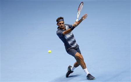 Federer of Switzerland hits a return during his men's singles tennis match against Djokovic of Serbia at the ATP World Tour Finals at the O2 Arena in London