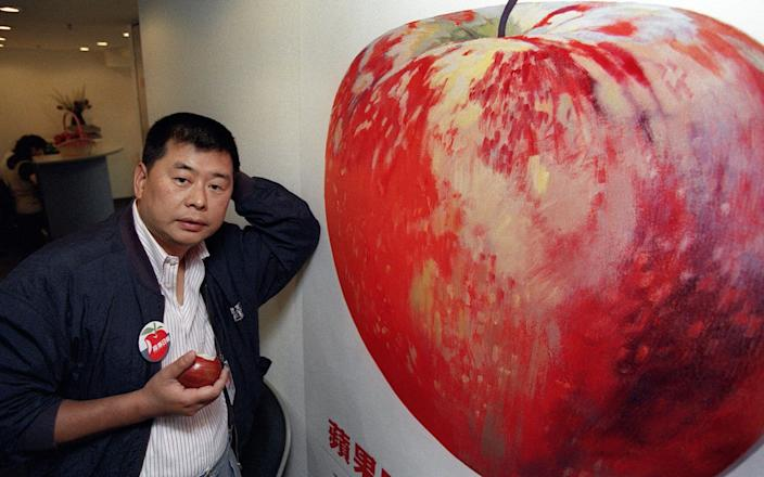 Hong Kong media tycoon Jimmy Lai posing at Apple Daily's new office in June 1995. Now, he is in jail and the paper is shutting down. - Mike CLARKE/ AFP