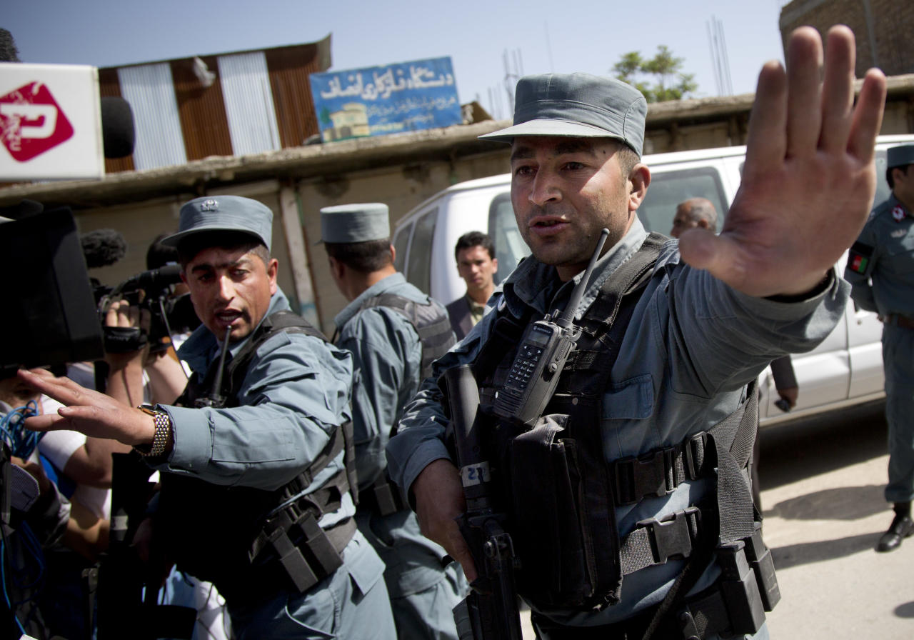 Afghan policemen stop people from approaching the scene where a suicide car bomber attacked a NATO convoy in Kabul, Afghanistan, Thursday, May 16, 2013. A Muslim militant group, Hizb-e-Islami, claimed responsibility for the early morning attack, killing many in the explosion and wounding tens, police and hospital officials said. The powerful explosion rattled buildings on the other side of Kabul and sent a pillar of white smoke into the sky in the city's east. (AP Photo/Anja Niedringhaus)