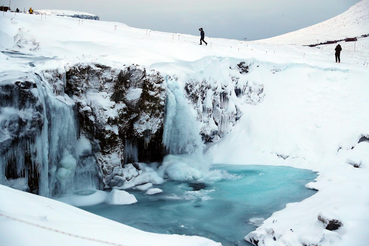 <p>People walk around the frozen five meter high Kirjufell waterfall on the west coast of Iceland. (PA) </p>