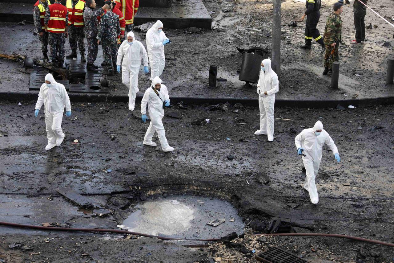 Forensic inspectors examine the site of an explosion in downtown Beirut December 27, 2013. Former Lebanese minister Mohamad Chatah, who opposed Syrian President Bashar al-Assad, was killed in the massive bomb blast which one of his political allies blamed on Lebanon's Shi'ite Hezbollah militia. REUTERS/Mohamed Azakir (LEBANON - Tags: POLITICS CIVIL UNREST)