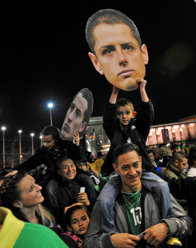 Soccer fans hold photos of soccer players before an international friendly soccer match between Mexico and Nigeria on Wednesday, March 5, 2014, in Atlanta. (AP Photo/David Tulis)