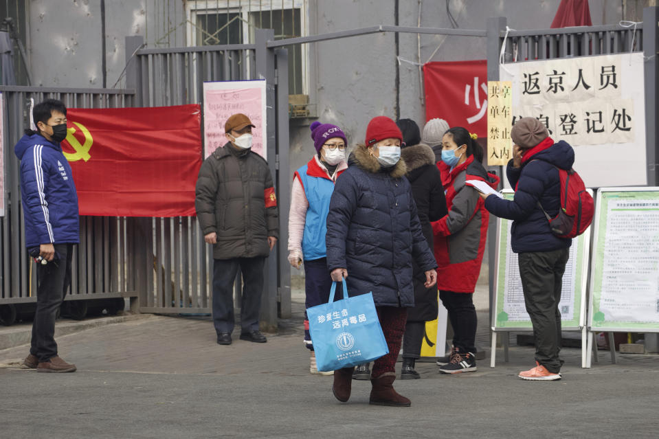 """Residents wait to enter a checkpoint with a sign which reads """"Returnees to Beijing registration point"""" in Beijing, China Thursday, Feb. 13, 2020. China is struggling to restart its economy after the annual Lunar New Year holiday was extended to try to keep people home and contain novel coronavirus. Traffic remained light in Beijing, and many people were still working at home. (AP Photo/Ng Han Guan)"""