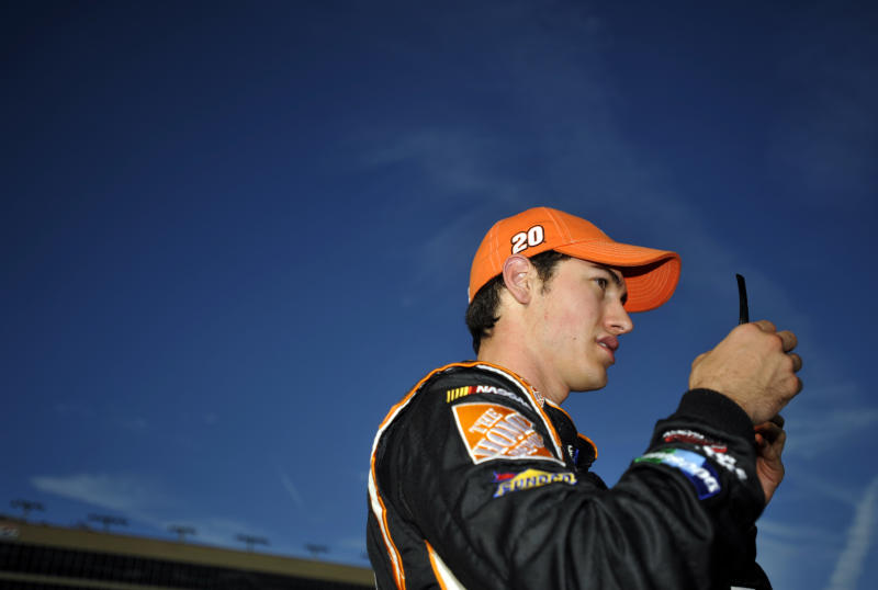 Joey Logano puts on his sunglasses after getting out of his car during qualifying for Sunday's NASCAR Sprint Cup Series auto race at Atlanta Motor Speedway, Friday, Aug. 31, 2012, in Hampton, Ga. (AP Photo/Rainier Ehrhardt)