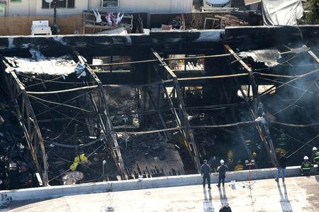 FILE PHOTO: Firefighters work inside the burned warehouse following the fatal fire in the Fruitvale district of Oakland