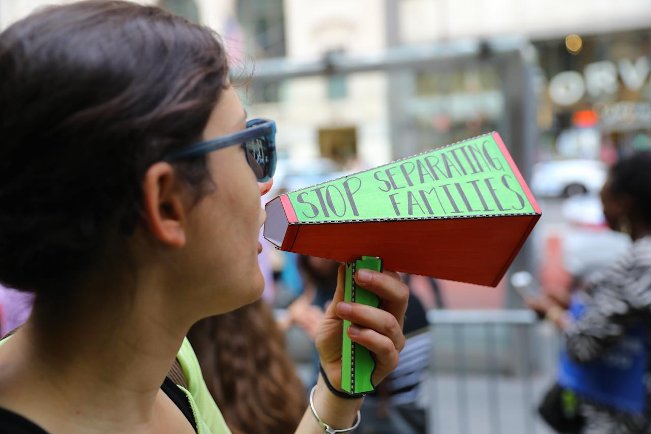 <p>A protester yells into a homemade megaphone during a protest outside the New York Public Library on 42nd Street in New York City on June 20, 2018. (Photo: Gordon Donovan/Yahoo News) </p>