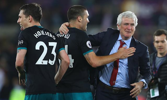 Mark Hughes celebrates with his players after Southampton's victory at Swansea took them to the verge of Premier League safety.