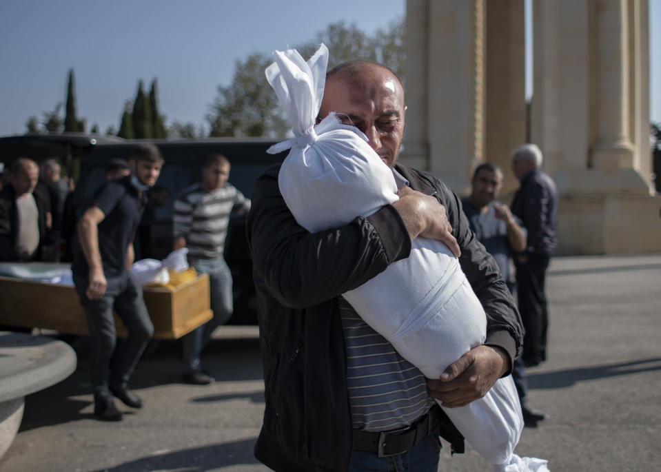 Timur Haligov, an Azerbaijani Turkish father embraces the body of his 10-month-old baby girl, Narin, who was killed by overnight shelling by Armenian forces. during a funeral ceremony, in Ganja, Azerbaijan, Saturday, Oct. 17, 2020. Azerbaijan has accused Armenia of striking its second-largest city with a ballistic missile that killed at least 13 civilians and wounded 50 others in a new escalation of their conflict over Nagorno-Karabakh. (Can Erok/DHA via AP)