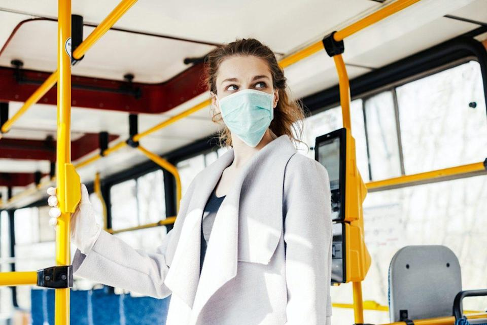 Woman wearing surgical protective mask pushing the button in a public transportation.