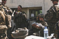 In this image provided by the U.S. Marine Corps, Marines assigned to the 24th Marine Expeditionary Unit (MEU) calm infants during an evacuation at Hamid Karzai International Airport in Kabul, Afghanistan, Friday, Aug. 20, 2021. (Sgt. Isaiah Campbell/U.S. Marine Corps vi AP)