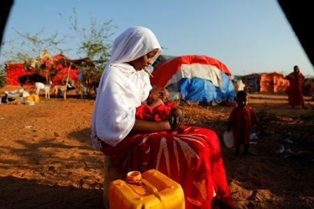 Zeinab, 14, sits as she holds her nephew at a camp for internally displaced people from drought hit areas in Dollow, Somalia April 4, 2017. REUTERS/Zohra Bensemra