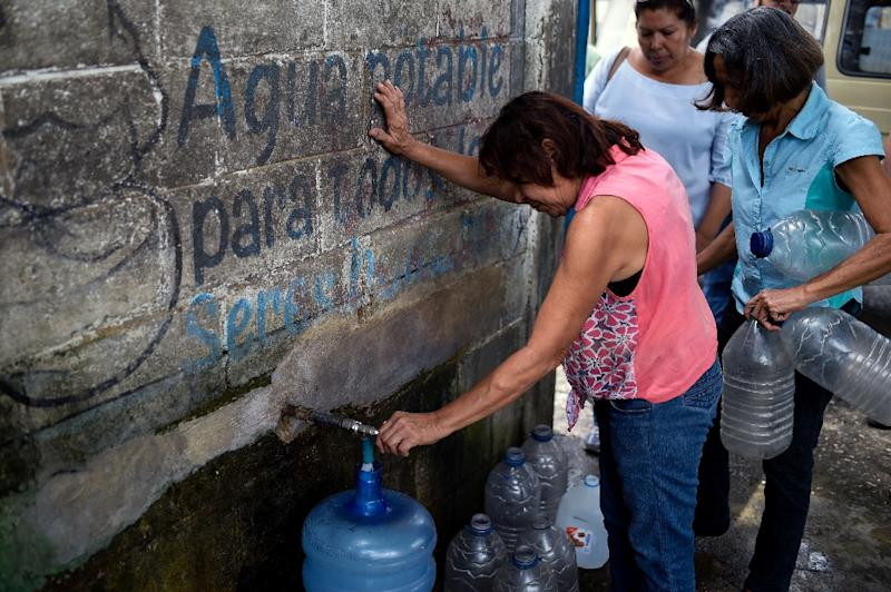 Many San Juan residents are obliged to trek to a well in the center of town to fill up water containers (AFP Photo/Federico PARRA)