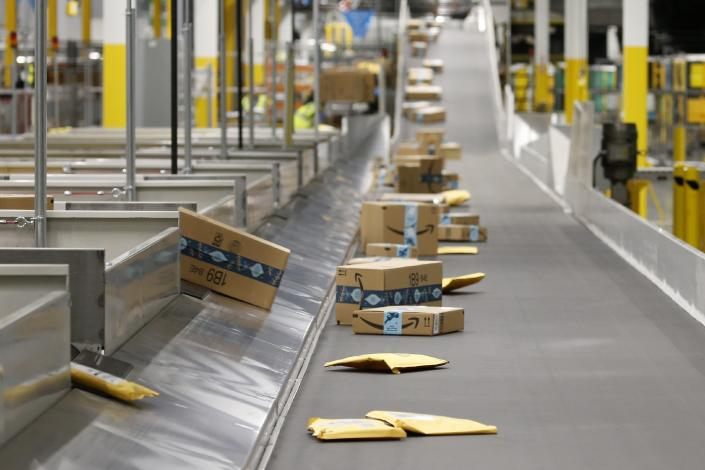 FILE - In this Dec. 17, 2019, file photo Amazon packages move along a conveyor at an Amazon warehouse facility in Goodyear, Ariz. In the years since Barack Obama and Joe Biden left the White House, the tech industry's political fortunes have flipped. Facebook, Google, Amazon and Apple have come under scrutiny from Congress, federal regulators, state attorneys general and European authorities. (AP Photo/Ross D. Franklin, File)