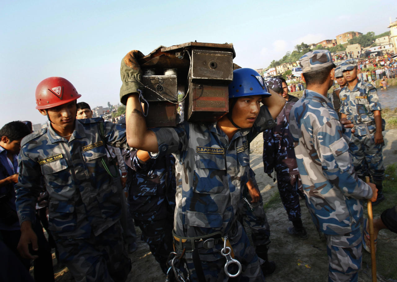 A Nepalese rescue worker carries the flight data recorder of a Sita Air airplane at the crash site near Katmandu, Nepal, early Friday, Sept. 28, 2012. The plane carrying trekkers into the Everest region crashed just after takeoff Friday morning in Nepal's capital, killing all 19 people on board, authorities said. (AP Photo/Niranjan Shrestha)